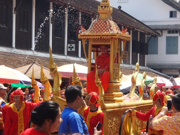 a senior monk in a parade during Pi Mai